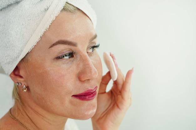 Jovem mulher com toalha de banho na cabeça aplicar tônico de limpeza com almofadas de algodão garota remover maquiagem com microfone ...