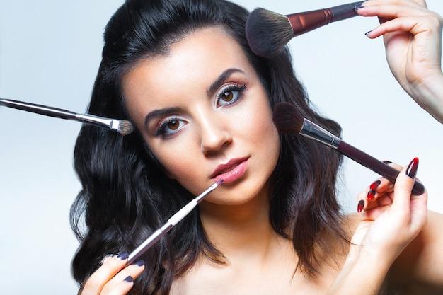Jovem mulher com todos os tipos de ferramentas de maquiagem
