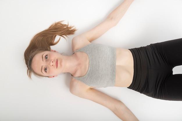 Jovem mulher com top esportivo e leggings encontra-se no chão branco após o treino. vista do topo. retrato em fundo branco.