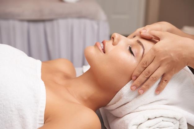Jovem mulher com tratamento anti-idade no salão spa