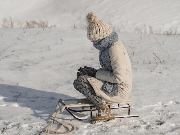 Jovem mulher com trenó vestida com roupas casuais de inverno. uma mulher sofrendo em um inverno frio ao ar livre.