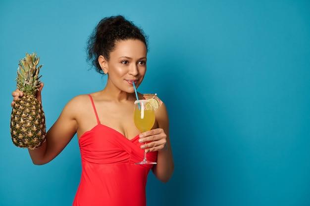 Jovem mulher com um abacaxi bebendo um delicioso coquetel exótico de canudo, posando