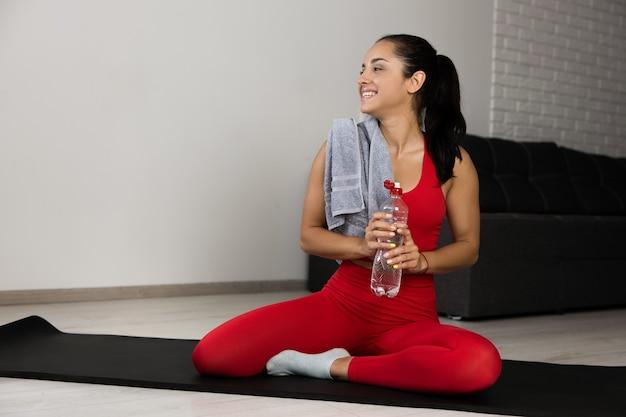Jovem mulher com um agasalho vermelho, fazendo exercícios ou ioga em casa. alegre menina positiva segurar a garrafa de água nas mãos e sorrir, olhando para a esquerda. mulher bem construída e desportiva sentada sozinha no tapete após o treino.