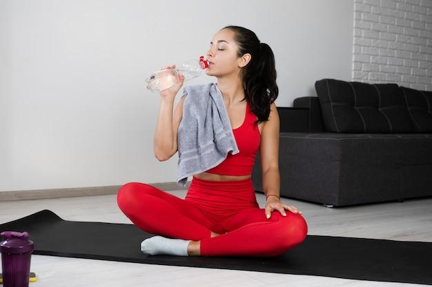 Jovem mulher com um agasalho vermelho, fazendo exercícios ou ioga em casa. sente-se na esteira e beba água. mulher desportiva relaxar ou descansar após o treino ou exercício no apartamento. tempo de hidratação.
