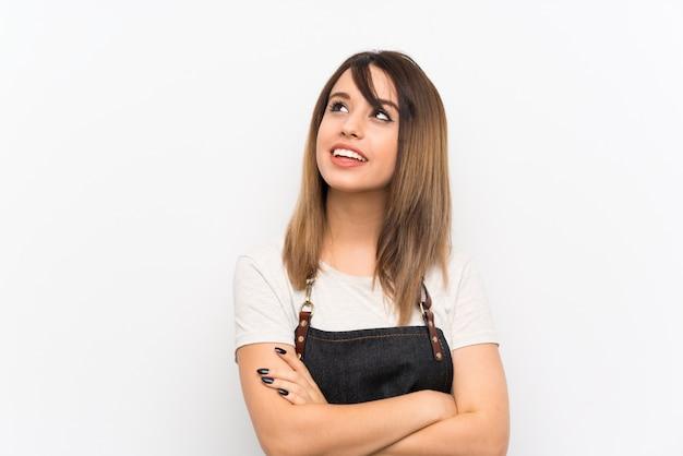 Jovem mulher com um avental, olhando para cima enquanto sorrindo