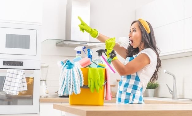 Jovem mulher com um balde de material de limpeza em uma mesa de cozinha vestida para o trabalho doméstico, cantando em uma escova de banheiro, apontando para a frente com uma mão em luvas de borracha.