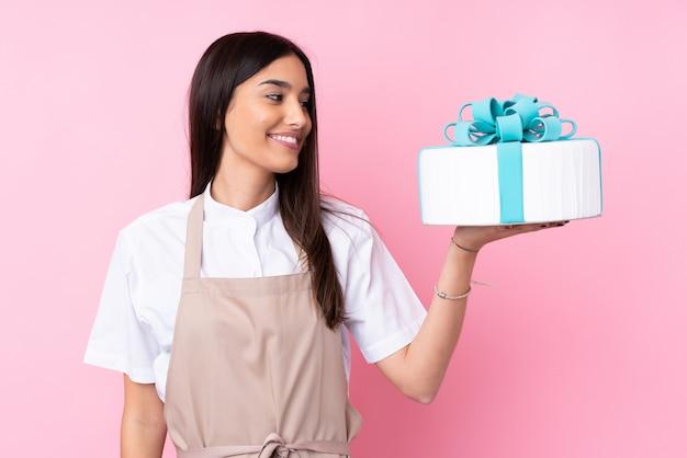 Jovem mulher com um bolo grande com expressão feliz