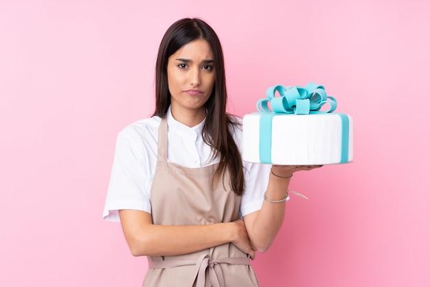 Jovem mulher com um bolo grande sobre parede isolada com expressão triste