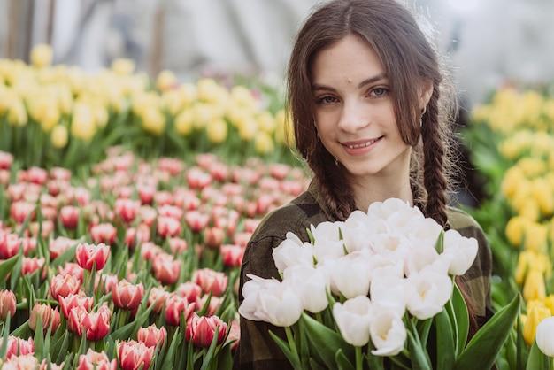 Jovem mulher com um buquê de tulipas de flores da primavera.