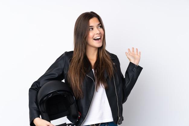 Jovem mulher com um capacete de moto sobre parede branca isolada com expressão facial de surpresa