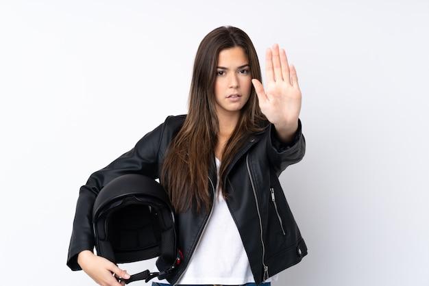 Jovem mulher com um capacete de moto sobre parede branca isolada, fazendo o gesto de parada com a mão