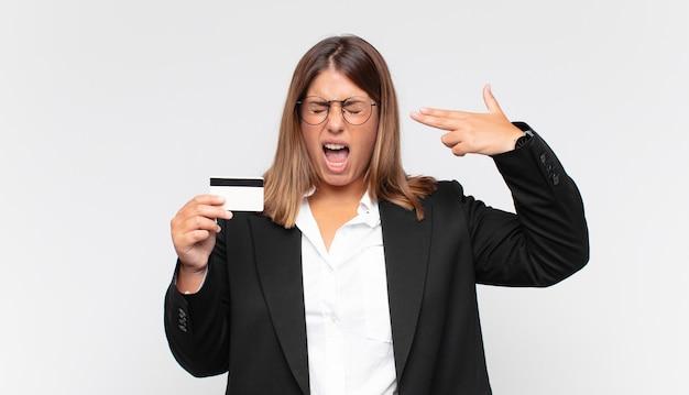 Jovem mulher com um cartão de crédito parecendo infeliz e estressada, gesto suicida fazendo sinal de arma com a mão, apontando para a cabeça