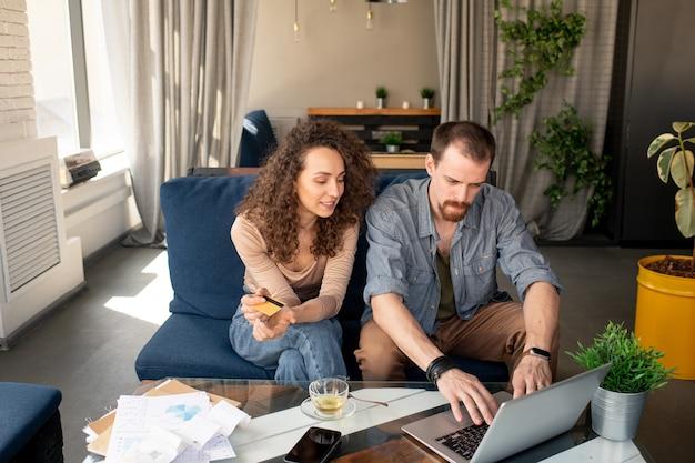 Jovem mulher com um cartão de plástico sentada no sofá ao lado do marido em frente ao laptop