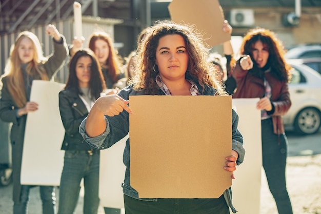 Jovem mulher com um cartaz em branco na frente de pessoas que protestam sobre os direitos das mulheres e a igualdade nas ruas. reunião sobre problemas no local de trabalho, pressão masculina, violência doméstica, assédio. copyspace.