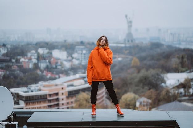 Jovem mulher com um casaco laranja posa no telhado de um edifício no centro da cidade