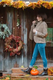 Jovem mulher com um casaco marrom quente e calça jeans em um fundo rústico.