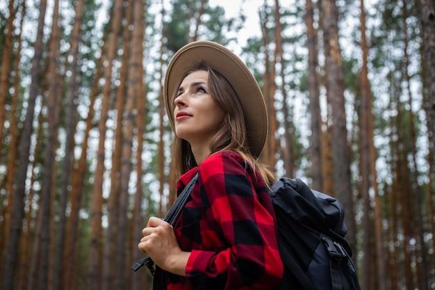 Jovem mulher com um chapéu, camisa vermelha e mochila olha para as copas das árvores em uma floresta de pinheiros. acampar na floresta.