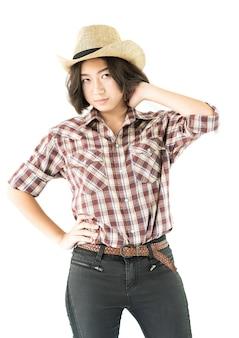 Jovem mulher com um chapéu de cowboy e camisa xadrez com a mão no chapéu