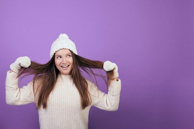 Jovem mulher com um chapéu de malha branca de inverno em uma camisola quente e luvas.