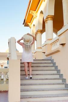 Jovem mulher com um chapéu de sol sobe as escadas