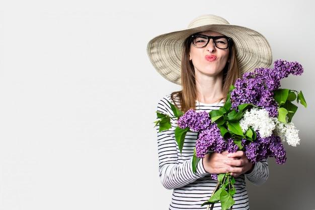 Jovem mulher com um chapéu e óculos caretas segurando um buquê sobre um fundo claro.