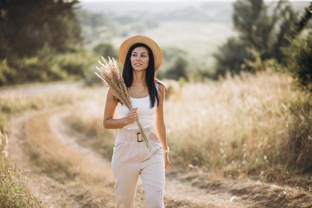 Jovem mulher com um chapéu em um campo de trigo