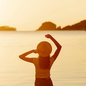 Jovem mulher com um chapéu no pôr do sol