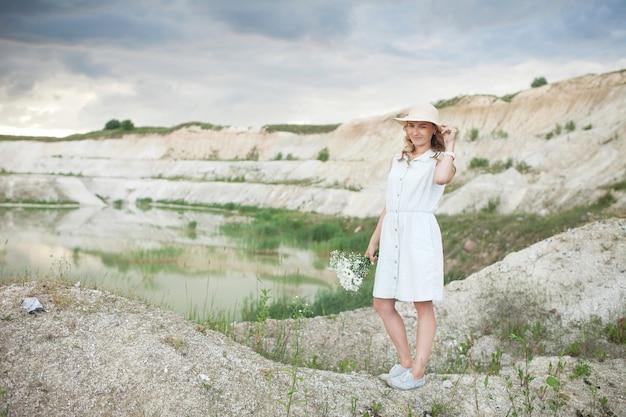 Jovem mulher com um chapéu perto de um lago com água leve e colinas arenosas.