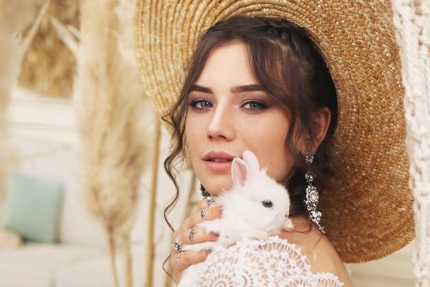 Jovem mulher com um coelho nas mãos dela, elegante retrato feminino elegante