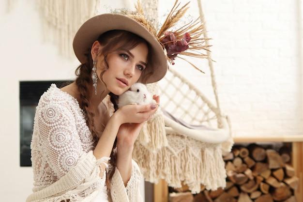 Jovem mulher com um coelho nas mãos dela