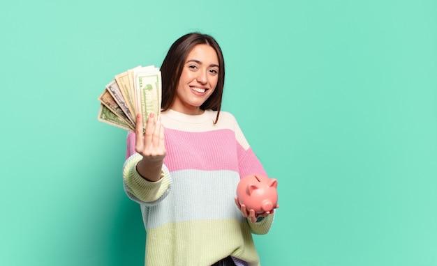 Jovem mulher com um cofrinho e notas de dólar