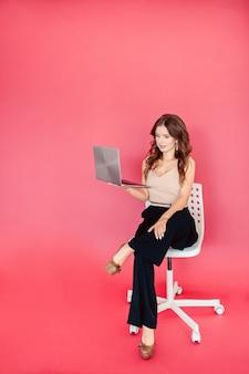 Jovem mulher com um computador portátil em uma parede rosa