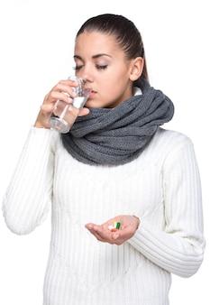 Jovem mulher com um copo de água tomando pílulas.