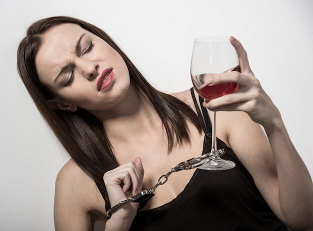 Jovem mulher com um copo de vinho e algemas.