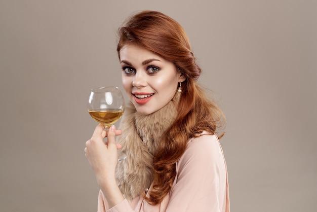 Jovem mulher com um copo de vinho em roupas vintage