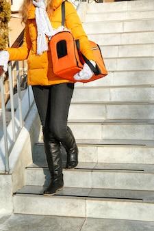 Jovem mulher com um gato na sacola na escada