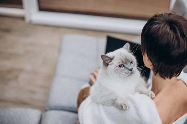 Jovem mulher com um gato trabalhando em um laptop de casa