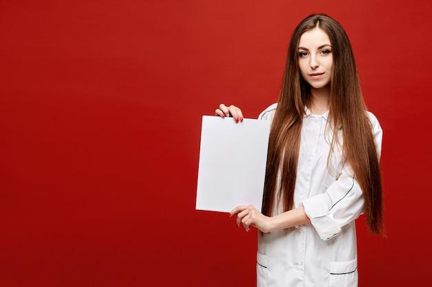 Jovem mulher com um jaleco branco com uma folha de papel branca vazia nas mãos dela. copie o espaço para o seu texto. conceito de cuidados de saúde e medicina