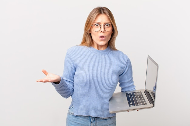 Jovem mulher com um laptop espantada, chocada e atônita com uma surpresa inacreditável
