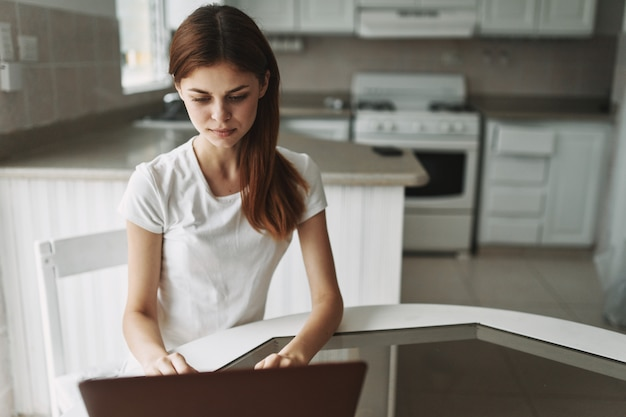 Jovem mulher com um laptop na mesa trabalhando e descansando