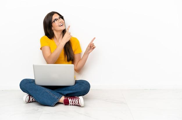 Jovem mulher com um laptop sentada no chão apontando com o dedo indicador uma ótima ideia