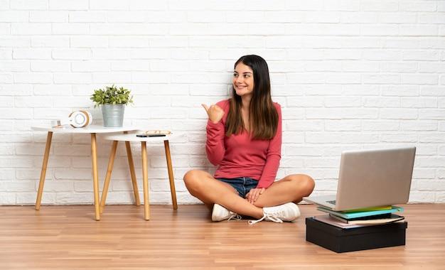Jovem mulher com um laptop sentado no chão dentro de casa, apontando para o lado para apresentar um produto