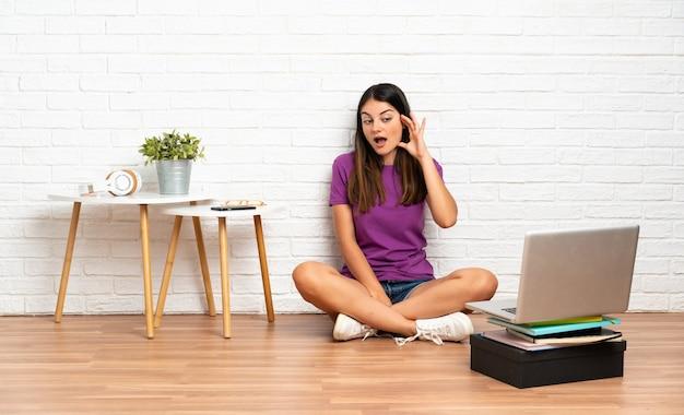 Jovem mulher com um laptop sentado no chão em ambientes fechados, ouvindo algo, colocando a mão na orelha