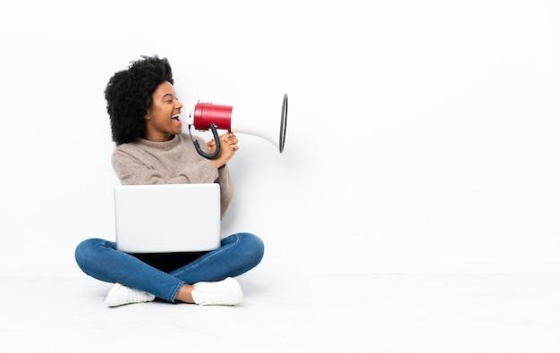 Jovem mulher com um laptop sentado no chão gritando através de um megafone