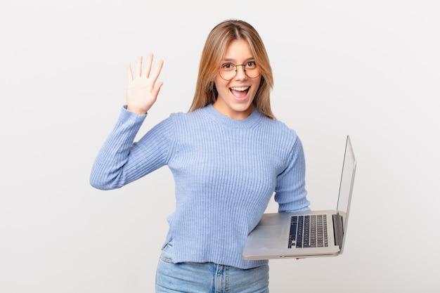 Jovem mulher com um laptop sorrindo feliz, acenando com a mão, dando as boas-vindas e cumprimentando você