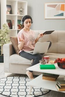 Jovem mulher com um laptop usando fones de ouvido, segurando um notebook com uma caneta, sentada no sofá atrás da mesa de centro na sala de estar