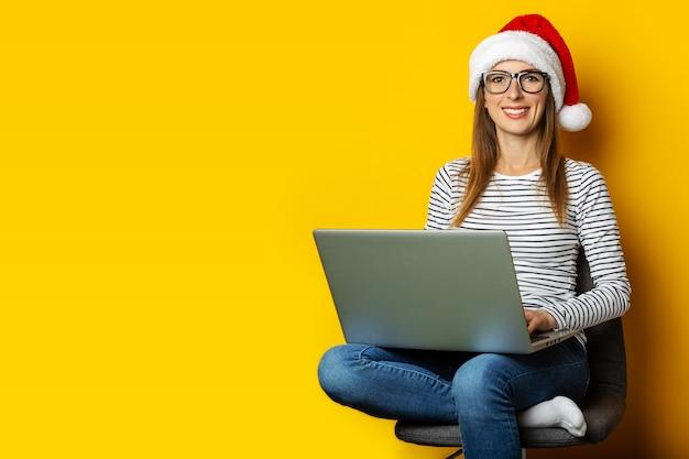 Jovem mulher com um laptop, usando um chapéu de papai noel e sentada em uma cadeira