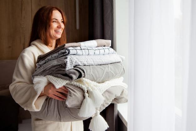 Jovem mulher com um lindo sorriso em um manto bege quente está encostada na pilha de lençóis dobrados em textura diferente. cama de algodão natural e orgânico. copie o espaço. fabricação. indústria hoteleira.