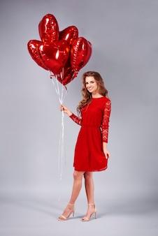 Jovem mulher com um monte de balões em forma de coração