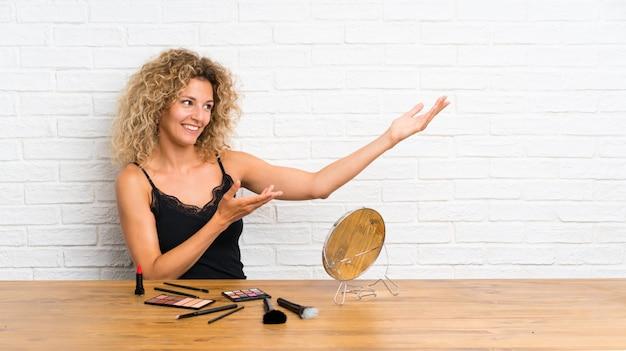 Jovem mulher com um monte de pincel de maquiagem em uma mesa, estendendo as mãos para o lado para convidar para vir